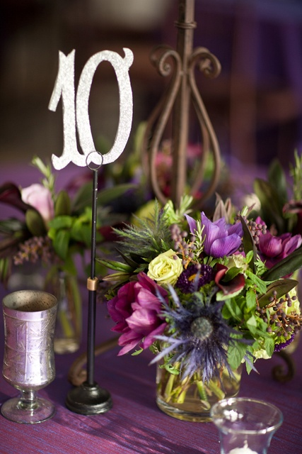 a colorful fall wedding centerpiece of purple and neutral blooms and greenery, candles and a table number over the arrangement