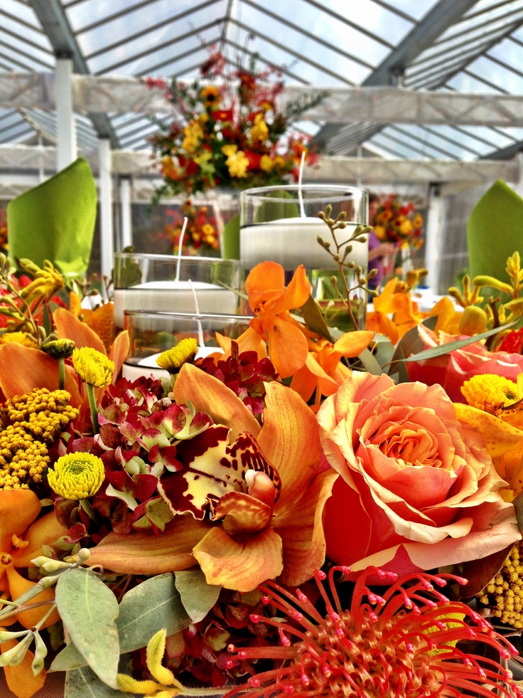 a bright and colorful fall flower centerpiece with a couple of floating candles is very bold and statement like