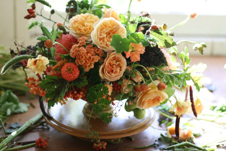 a fine art fall wedding centerpiece or orange, red and peachy blooms, greenery and foliage is lovely for fall