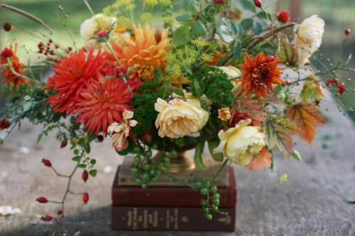 a bright fall wedding centerpiece of orange, red and rust blooms, creamy flowers and textural greenery