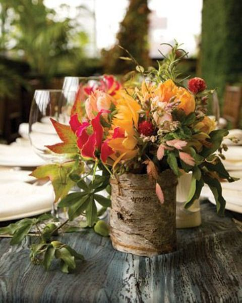 a fall wedding centerpiece of bright blooms and greenery in a stump is a cool woodland or rustic fall centerpiece