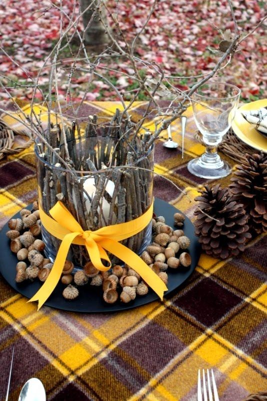 a creative fall wedding centerpiece of a black plate, nuts and acorns, a candleholder covered with sticks and branches and a yellow ribbon