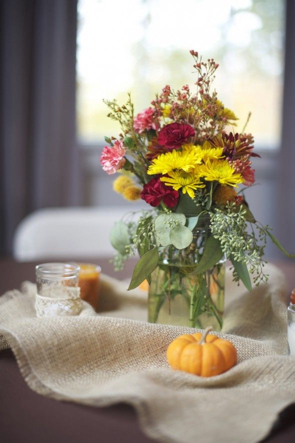 a bright fall wedding centerpiece of burlap, little pumpkins, candles, a jar with bright blooms and greenery will bring a rustic feel