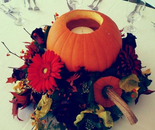 a bright fall wedding centerpiece of bold blooms, dark foliage, twigs and a cutout pumpkin with a candle inside