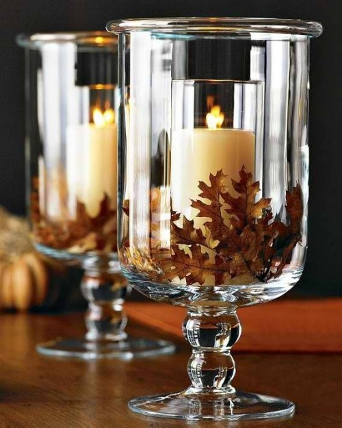 glasses with dried fall leaves and candles inside are stylish and simple fall wedding centerpieces