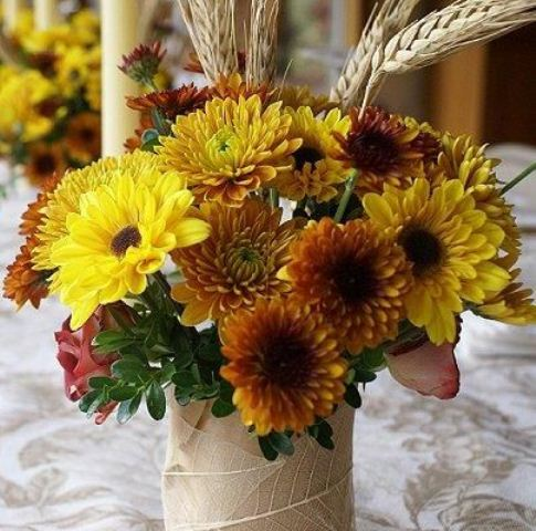 a bright rustic fall wedding centerpiece of mustard and lemon blooms and greenery is cute