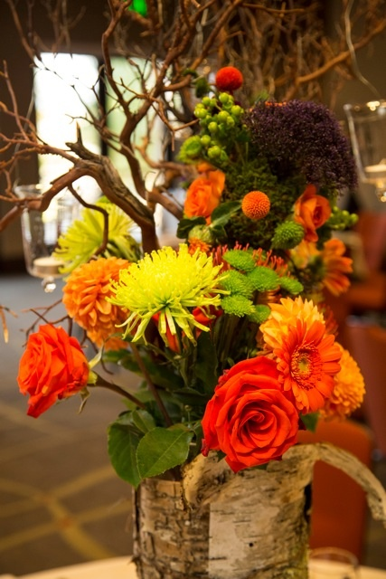 a bright fall wedding centerpiece of red, orange, lemon yellow blooms, berries and branches is bold and cool