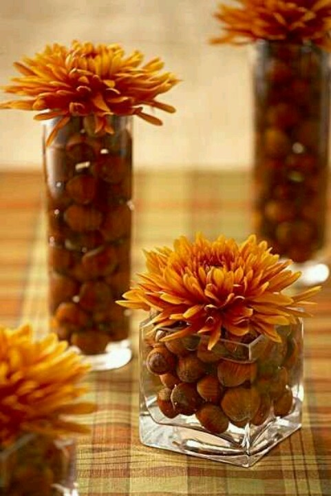 jars and tall glasses with nuts and acorns and bright blooms on top will compose a lovely and unusual fall wedding centerpiece