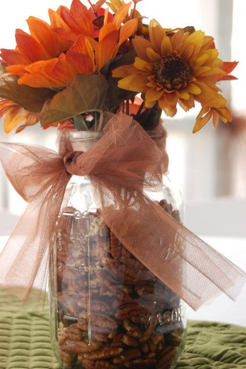 a rustic fall wedding centerpiece of a jar filled with walnuts, bright blooms and a sheer brown ribbon bow