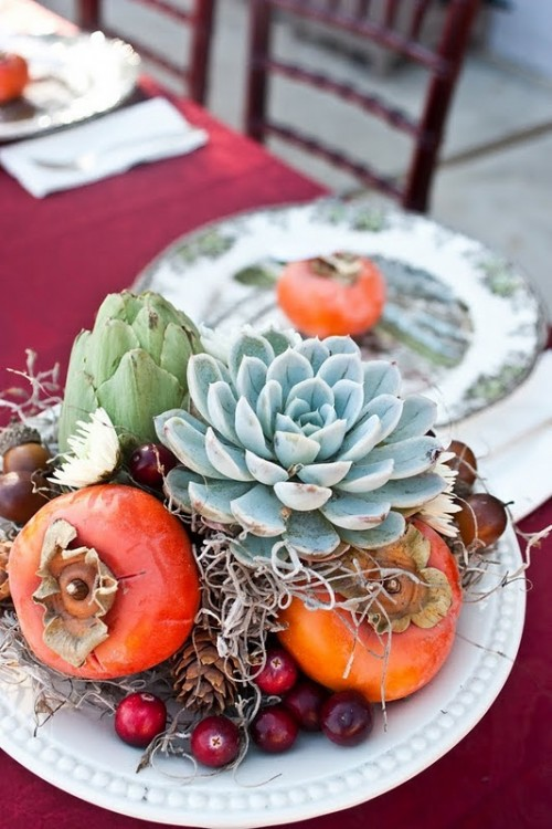 a creative fall wedding centerpiece of fruit, artichokes, a large succulent and berries looks yummy and fall-like