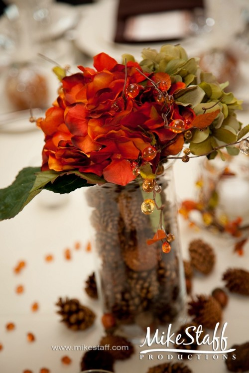 a bold fall wedding centerpiece of a tall glass with pinecones and nuts, bright blooms and foliage and some beads
