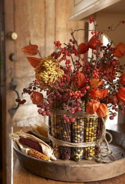 a bold and dried fall wedding centerpiece of corn cobs, dried blooms and some berries is simple and won't wither