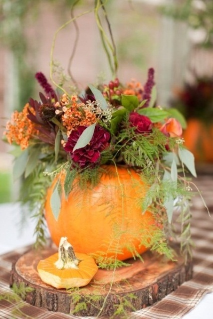 a pumpkin with greenery and ferns and bold blooms and berries is a cool fall wedding centerpiece