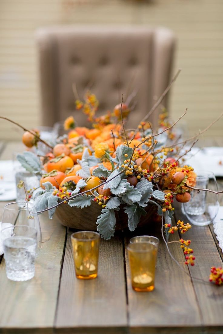a wooden bowl with pale foliage, fruits and branches with berries is a simple and cool rustic fall wedding centerpiece