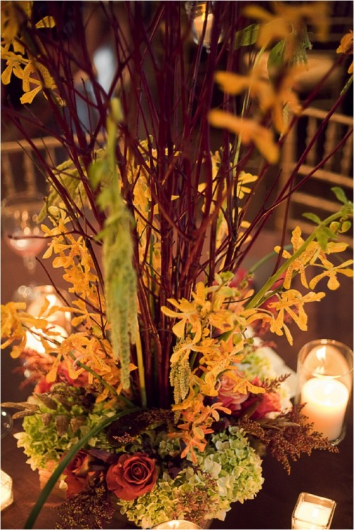a bright and textural fall flower and branches centerpiece surrounded with candles is a classic idea for a fall wedding