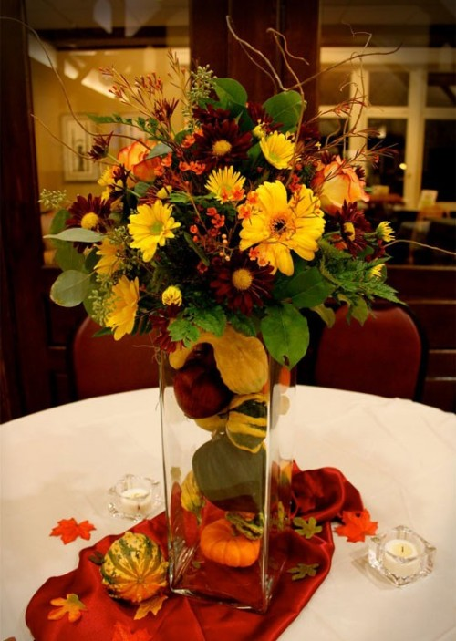 a super bold and textural wedding centerpiece with mini pumpkins in the vase and super bold blooms and twigs for a fall wedding