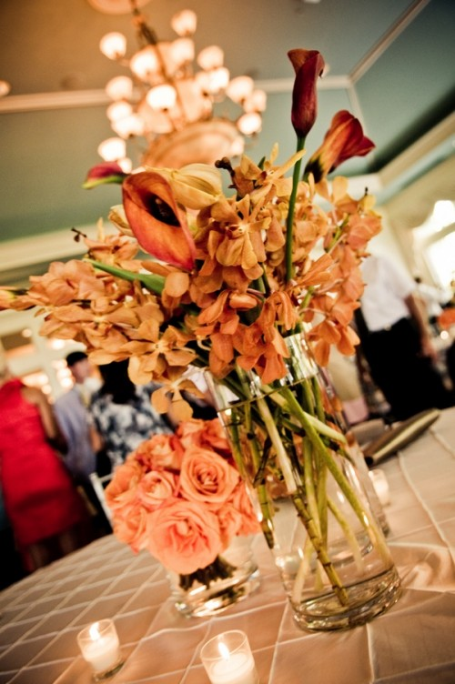 a colorful floral centerpiece of bright fall blooms and candles around is a nice idea for a colorful fall wedding