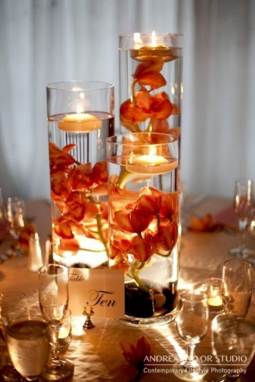 tall glasses with bright blooms and floating candles on top and candles around for a fall wedding