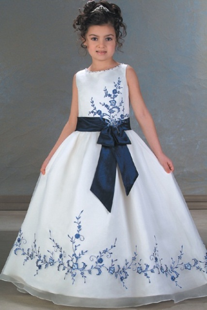 a white sleeveless A line flower girl dress with navy floral patterns and a navy sash and a bow is very bold