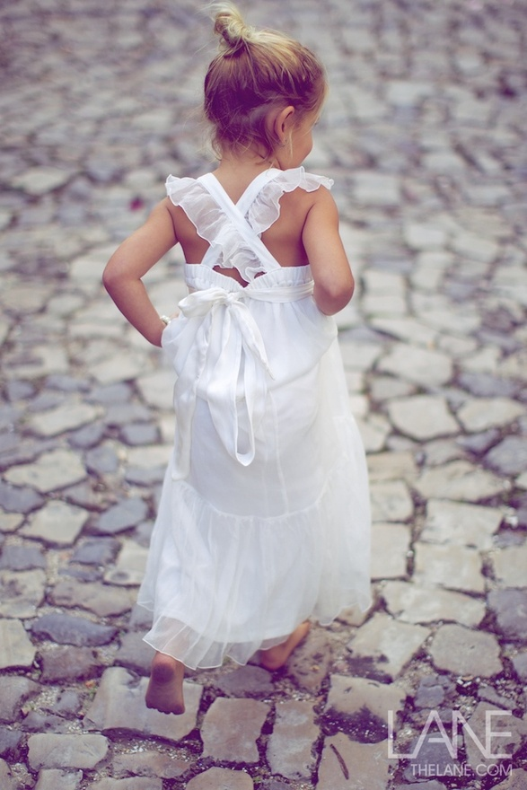 a relaxed white A line flower girl maxi dress with ruffles and a bow on the back is a lovely idea for a summer wedding