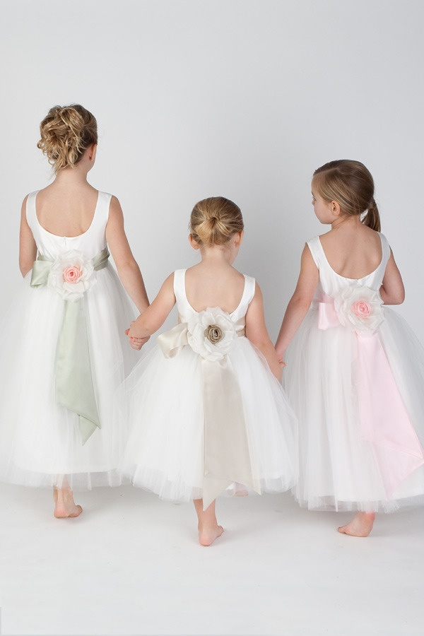 white and blush sleeveless flower girl dresses with cutout backs, flowers and ribbons on the backs for a refined look