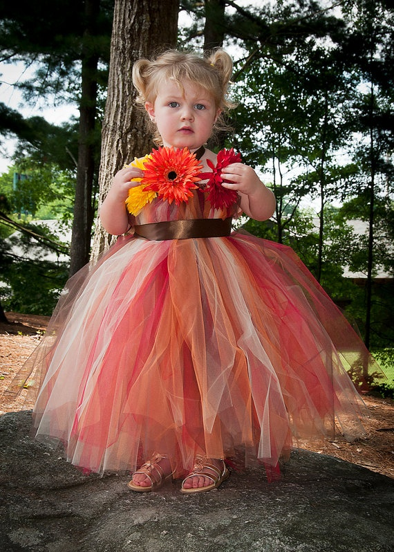 a strapless red, brown, rust and white tulle flower girl dress with a sash and bold blooms decorating the bodice for a fall wedding