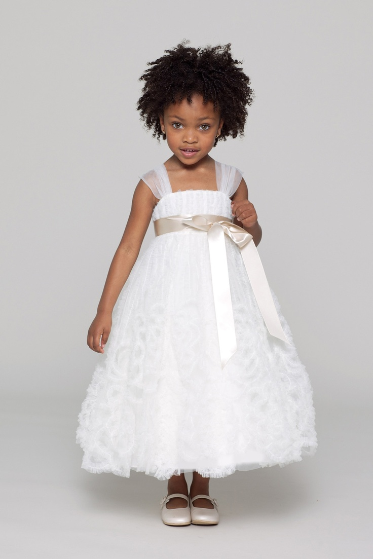 a white A line flower girl dress with sheer cap sleeves, a sash and a floral skirt is a bold and cool solution