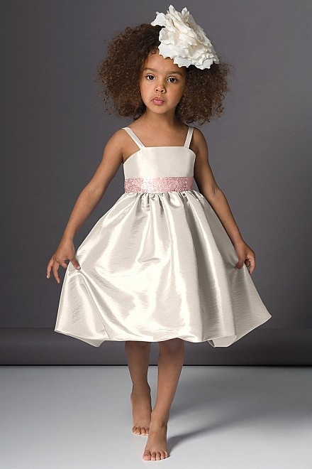 a neutral shiny flower girl dress with straps, a pink sash and a pleated skirt is a stylish and cute idea