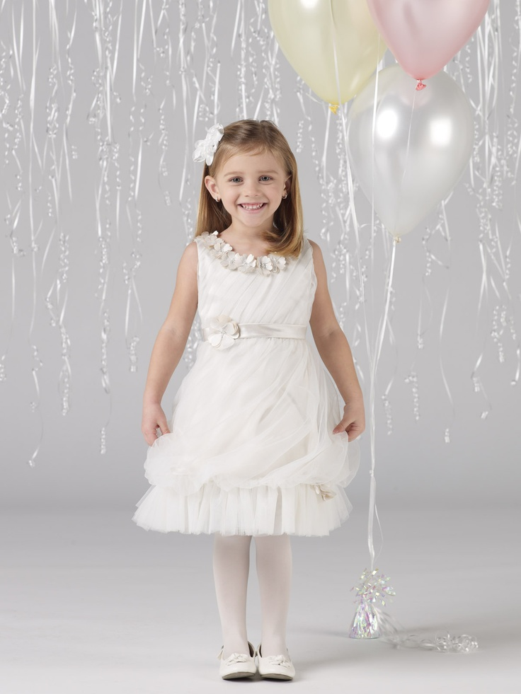 a white layered flower girl dress with a floral neckline and a sash plus a floral headpiece for a beautiful girlish look