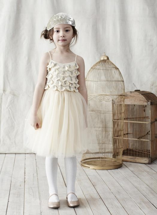 a neutral short vintage flower girl dress with a ruffle and embellished bodice and a tulle skirt for a vintage look