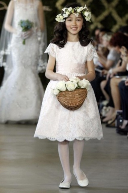 a white lace midi dress with short sleeves, a high neckline, a pink sash and white tights and flats for a classic flower girl look