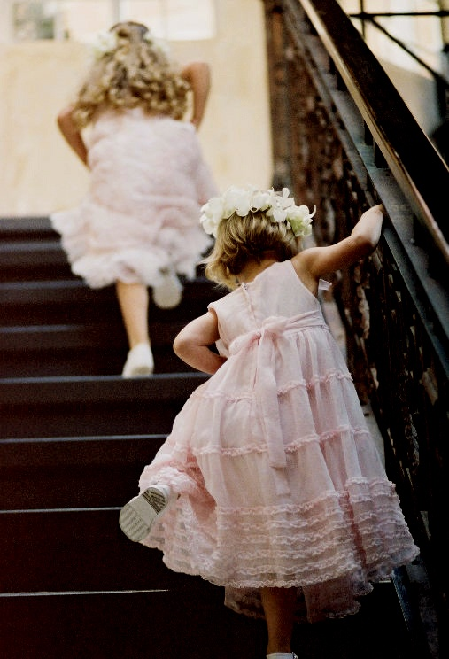 a sleeveless pink midi flower girl dress with ruffles and a floral headpiece for a beautiful and chic look