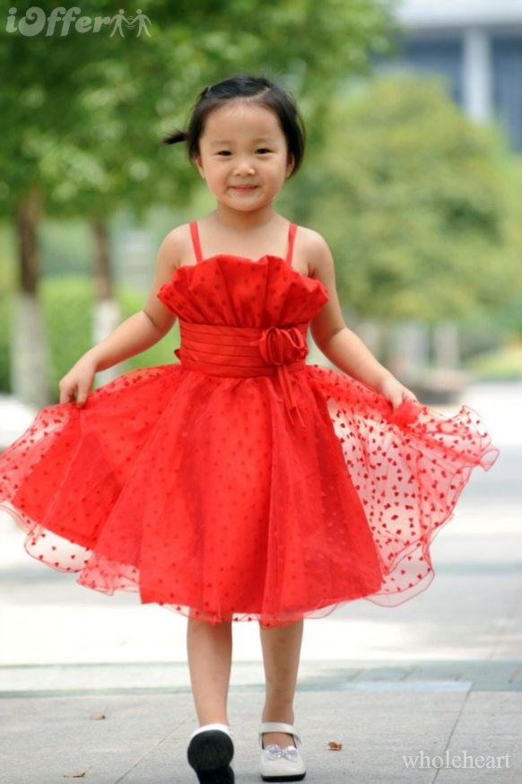 a red polka dot flower girl dress with a ruffle bodice and a layered skirt, spaghetti straps for a bold touch of color