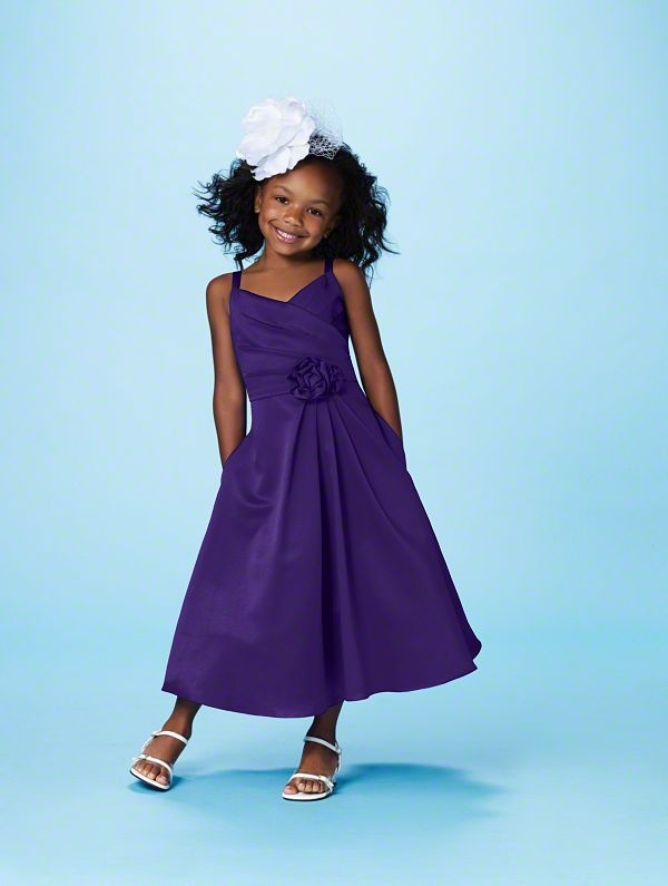 a purple A line midi dress with a pleated skirt, a layered bodice and a fabric flower for a bold touch