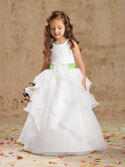a white sleeveless flower girl ballgown with a layered ruffle skirt and a sleek bodice, a green sash for a beautiful classic look
