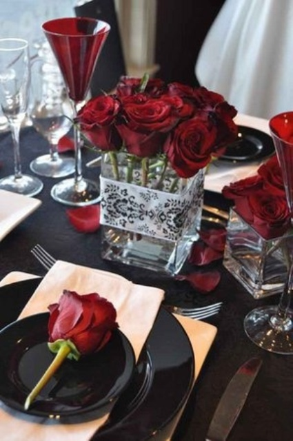 a stylish wedding centerpiece of red roses in a jar is a very cool and bold statement at the table