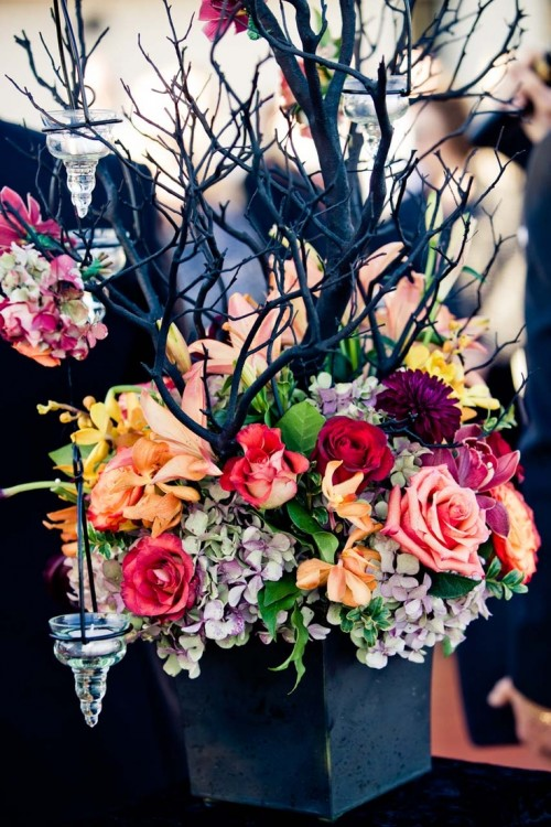 a moody Halloween wedding centerpiece of a black planter, bold blooms, black branches, greenery and candleholders on the branches is very stylish