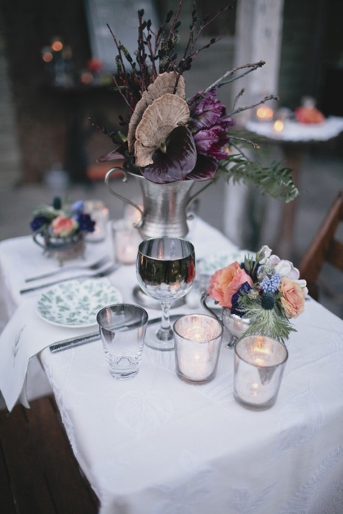 a bold and moody Halloween wedding centerpiece of a metal jug, purple blooms, branches and dried touches is a statement idea