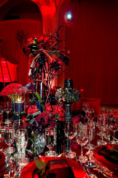 a dramatic Halloween wedding centerpiece in black and red, with branches, red blooms and black candles plus floral arrangements
