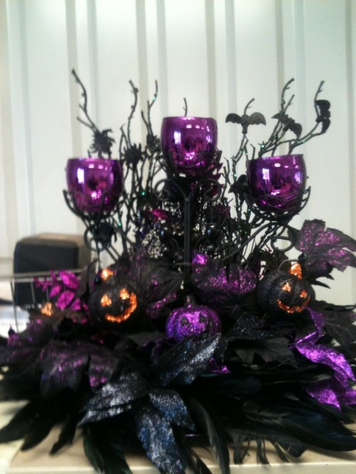 a dramatic black, purple and orange glitter Halloween wedding centerpiece with leaves, twigs and bats