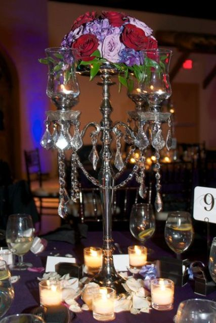 a refined Halloween wedding centepiece of a black candelabra with bold blooms on top and some crystals