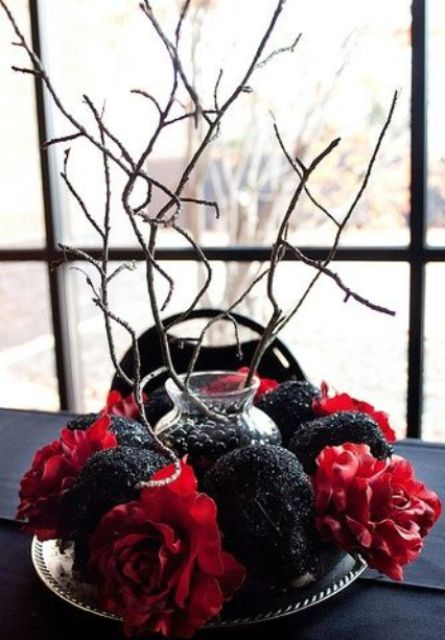 a dramatic Halloween wedding centerpiece of black glitter skulls, red flowers and branches going up is a very cool and bold idea