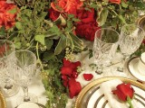 a chic Valentine's Day wedding table with greenery, red and burgundy roses, gold rimmed plates, red roses and crystal glasses