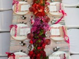 a bold Valentine's Day wedding table with an ombre tablecloth, a bold ombre floral table runner, ombre napkins, ribbons and a simple menus