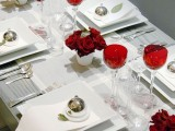 a stylish Valentine's Day wedding table in white, with metallic touches, red glasses and a red rose arrangement is very elegant and very chic