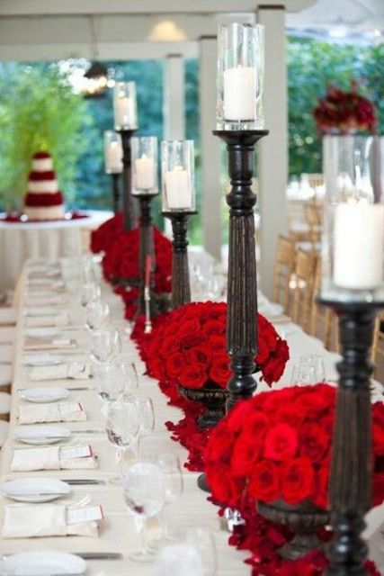 a stylish vintage Valentine's Day wedding table in neutrals, with dark wooden candleholders and white candles, red roses and silver is amazing