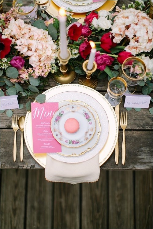 a beautiful Valentine's Day wedding table with a lush greenery, blush and fuchsia runner, white candles in gold candleholders, gold cutlery and stacked plates plus pink menus