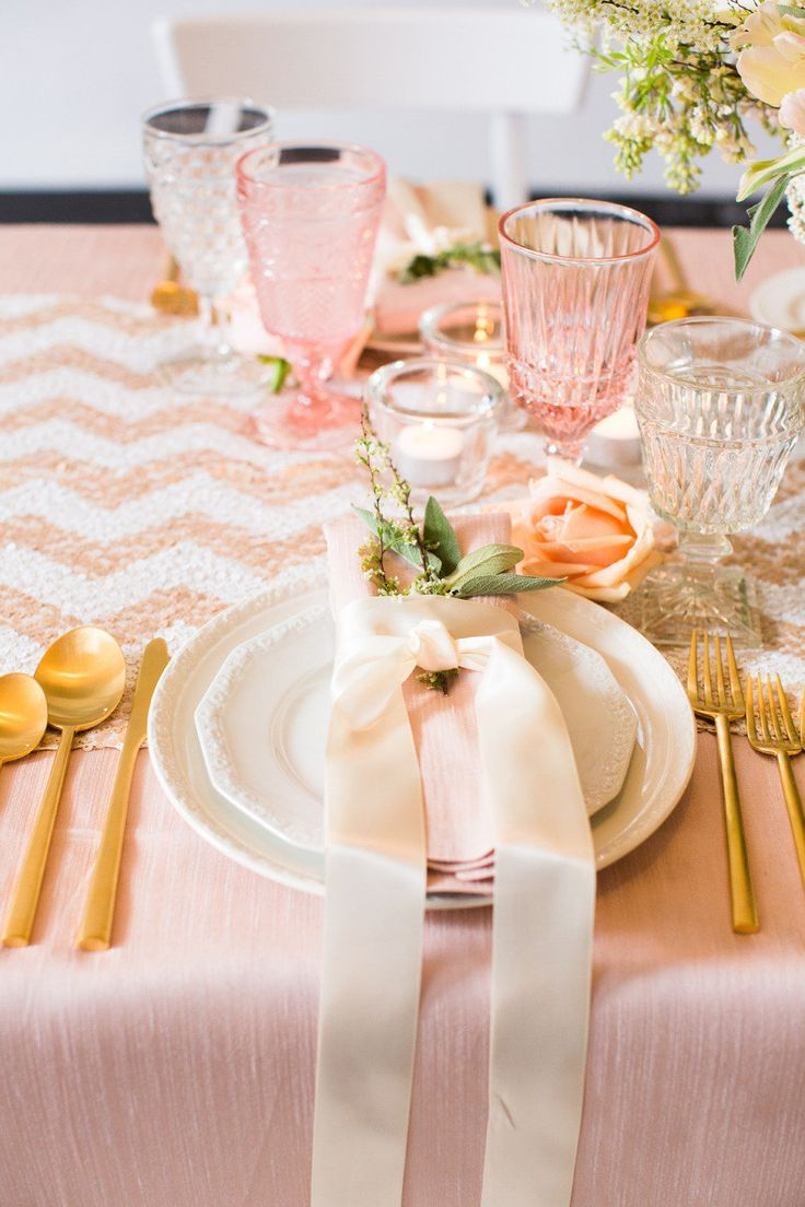 a romantic Valentine's Day wedding table with a chevron runner, a blush tablecloth, pink glasses, gold cutlery and some neutral blooms