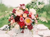 a grey polka dot tablecloth, white porcelain, blush napkins and glasses and a bold floral arrangement with greenery and grasses