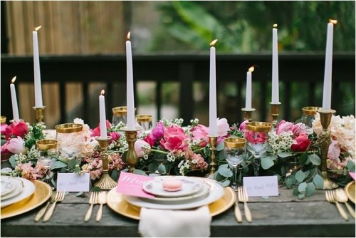 a chic and elegant Valentine's Day wedding table with a lush greenery, hot pink and white blooms, candles in brass candleholders, gold chargers and cutlery and printed plates